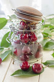 Ripe maroon cherries in a glass vase and a jar Stock Photography