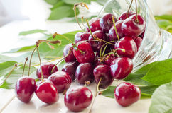 Ripe maroon cherries in a glass vase and a jar. Ripe and fresh burgundy cherries in a glass vase and a jar for healthy food and preparations for the winter Stock Photo