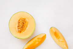 Ripe melon half and slices. On white background, top view, blank space royalty free stock photography