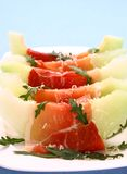Ripe melon with ham, parmesan cheese on white plate Stock Photos