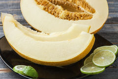 Ripe melon and lime on a black plate  old boards. Ripe melon and lime on a black ceramic plate on old boards Royalty Free Stock Photo
