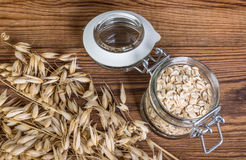 Ripe natural oat and flakes on a table. Detail of natural grains and rolled oats in jar on wooden background stock photos