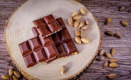 Ripe Nuts and Biiter Chocolate Wood Background. Nuts and Chocolate Concept and Decoration Stock Images