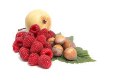 Ripe nuts,pear and raspberries on a white. Stock Images
