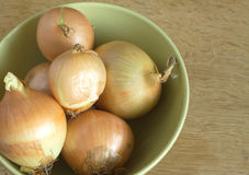 Ripe onions in green bowl on wooden surface top view Royalty Free Stock Photo