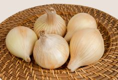 Ripe onions on a wicker plate Stock Photos
