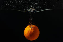 Ripe orange falling into the water with a splash Royalty Free Stock Image