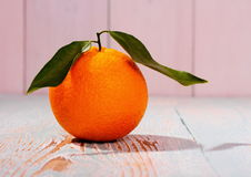 Ripe orange fruit with leaf on wooden board Stock Image
