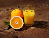 Ripe orange fruits and juice in glass Stock Photos
