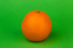Ripe orange on a green background. Juicy ripe orange on a bright green background Royalty Free Stock Photos