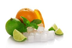Ripe orange, green lime and mint. Ripe orange and juicy green lime, mint and the cubes of ice isolated on the white Royalty Free Stock Images