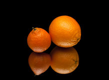 Ripe orange and mandarin on a black background with reflection Stock Photography