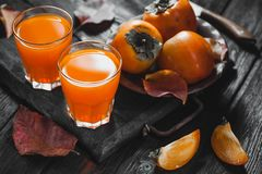 Ripe orange persimmon fruit and persimmon leaves in a brown plate on a black wooden table royalty free stock photography