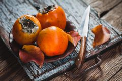 Ripe orange persimmon fruit and persimmon leaves in a brown plate on a brown wooden table stock images