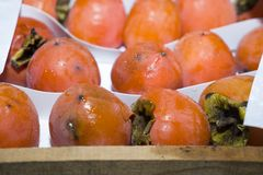 Ripe orange persimmon lies on white paper in a box for sale in a store, Royalty Free Stock Image