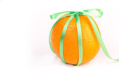 Ripe orange with satin ribbons. Bright ripe orange with satin ribbon on a white background Stock Photography