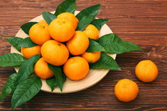 Ripe orange tangerines with green leaves in plate Royalty Free Stock Image