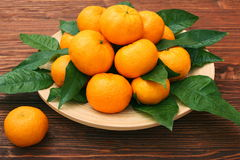 Ripe orange tangerines with green leaves in plate Stock Photo