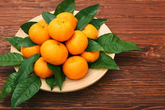 Ripe orange tangerines with green leaves in plate Royalty Free Stock Photography