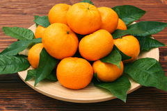 Ripe orange tangerines with green leaves in plate Royalty Free Stock Photos