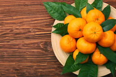 Ripe orange tangerines with green leaves in plate Stock Image