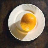 Ripe orange in white plate Stock Images