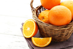 Ripe oranges. In basket on white wooden background stock photos