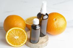 Ripe oranges and brown cosmetics bottles on wooden board.Concept of orange oil and cosmetics procedures royalty free stock photo