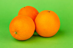 Ripe oranges on a green background. Juicy ripe oranges on a bright green background Royalty Free Stock Photography