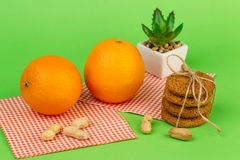 Ripe oranges, peanuts, oatmeal cookies and aloe. On a green background Royalty Free Stock Photos
