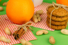 Ripe oranges, peanuts, oatmeal cookies and cinnamon sticks. On a green background Stock Image