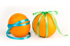 Ripe oranges with satin ribbons. Bright ripe oranges with satin ribbons on a white background Stock Image