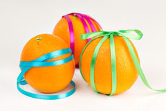Ripe oranges with satin ribbons. Bright ripe oranges with satin ribbons on a white background Stock Images