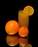 Mandarin, orange and glass of juice on a black background Stock Images