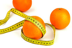 Ripe oranges and tape measure. Bright ripe oranges and tape measure on a white background Royalty Free Stock Photos