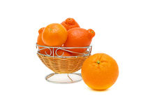 Ripe oranges on a white background. Isolated. One orange and tangerine in a basket on a white background. Isolation Royalty Free Stock Image
