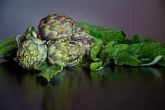 Ripe Organic Artichokes on a wooden table Stock Photo