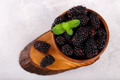 Ripe organic blackberries. In wooden bown on gray stone background Stock Photography
