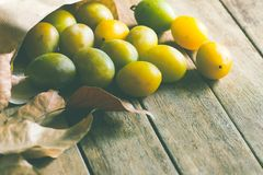 Ripe organic colorful yellow and green plums in brown craft paper bag scattered on plank wood background. Dry leaves. Stock Image