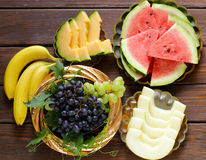 Ripe organic fruit watermelon, melon cantaloupe and grapes on a wooden table Stock Photo