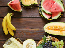 Ripe organic fruit watermelon, melon cantaloupe and grapes on a wooden table Royalty Free Stock Images