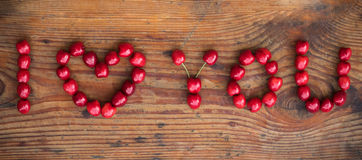 Ripe organic homegrown cherries, I love you text. Ripe organic homegrown cherries on wooden background, I love you text Royalty Free Stock Images
