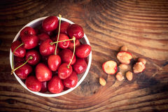 Ripe organic homegrown cherries and stones in a vintage ceramic bowl Royalty Free Stock Photography