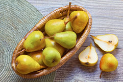 Ripe organic pears in basket. On wooden table and napkin with some sliced pears Royalty Free Stock Photos