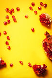 Ripe organic pomergranate and garnet seeds on yellow background. Healthy food or diet concept.Copy space Royalty Free Stock Photo