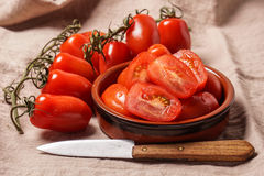 Ripe Organic red plum tomatoes. There is some whole tomatoes and other cut in a bowl stock images