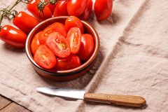 Ripe Organic red plum tomatoes. There is some whole tomatoes and other cut in a bowl stock photo