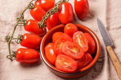 Ripe Organic red plum tomatoes. There is some whole tomatoes and other cut in a bowl royalty free stock photo