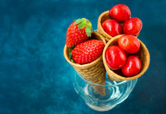 Ripe organic strawberries glossy sweet cherries in waffle ice cream cones in glass, dark blue background, healthy f Royalty Free Stock Images