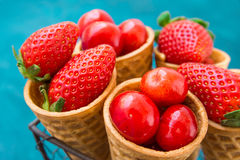 Ripe organic strawberries, glossy sweet cherries in waffle ice cream cones in wire basket, blue background, styled image Royalty Free Stock Image